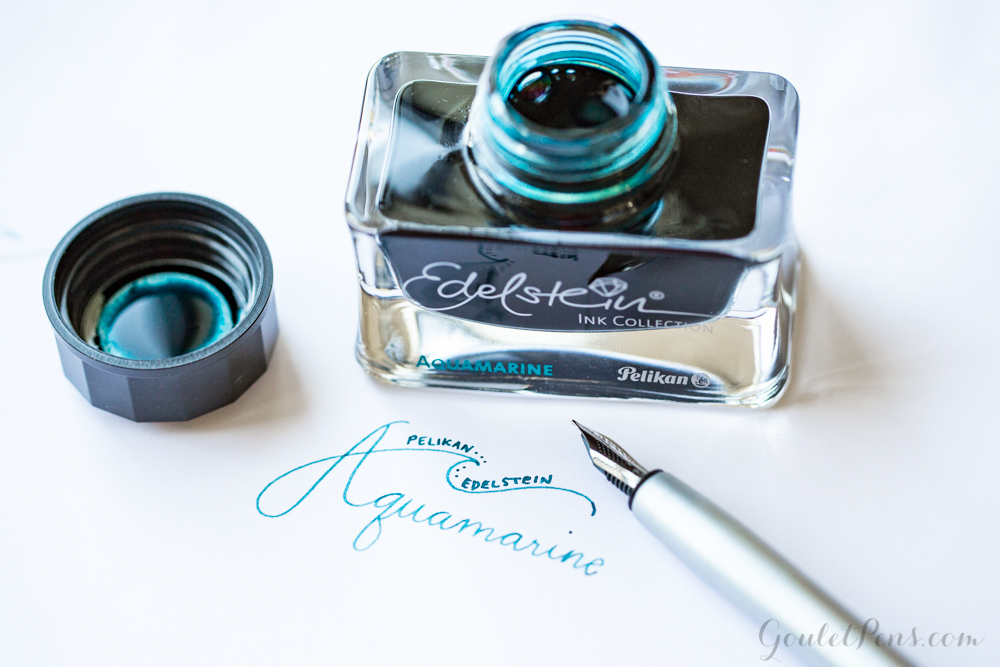 Pelikan Edelstein Aquamarine (50ml Bottled Ink) with a writing sample next a Faber-Castell Loom fountain pen.