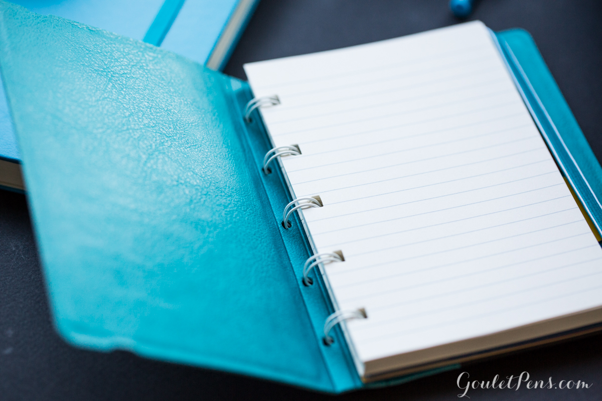 A pocket sized Filofax Aqua notebook with lined pages showing.