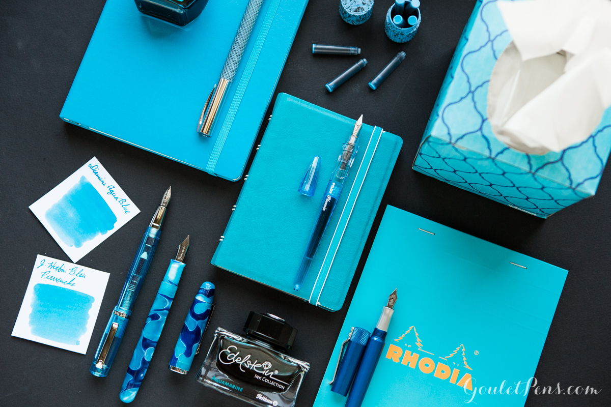 Neatly organized turquoise and aqua fountain pens, paper, and ink in a knolling style flatlay.
