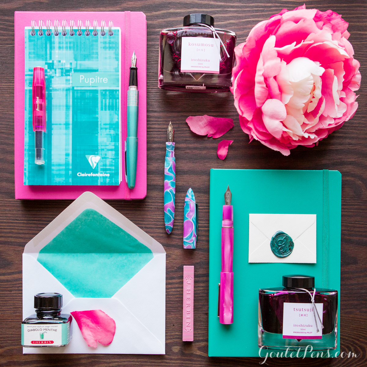 Turquoise and pink fountain pens, paper, and ink neatly organized in a knolling flatlay