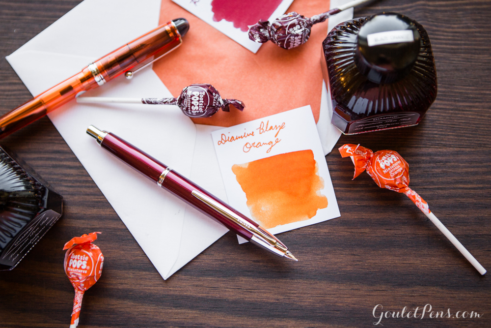 maroon and orange fountain pen, ink, and envelope with lollipops