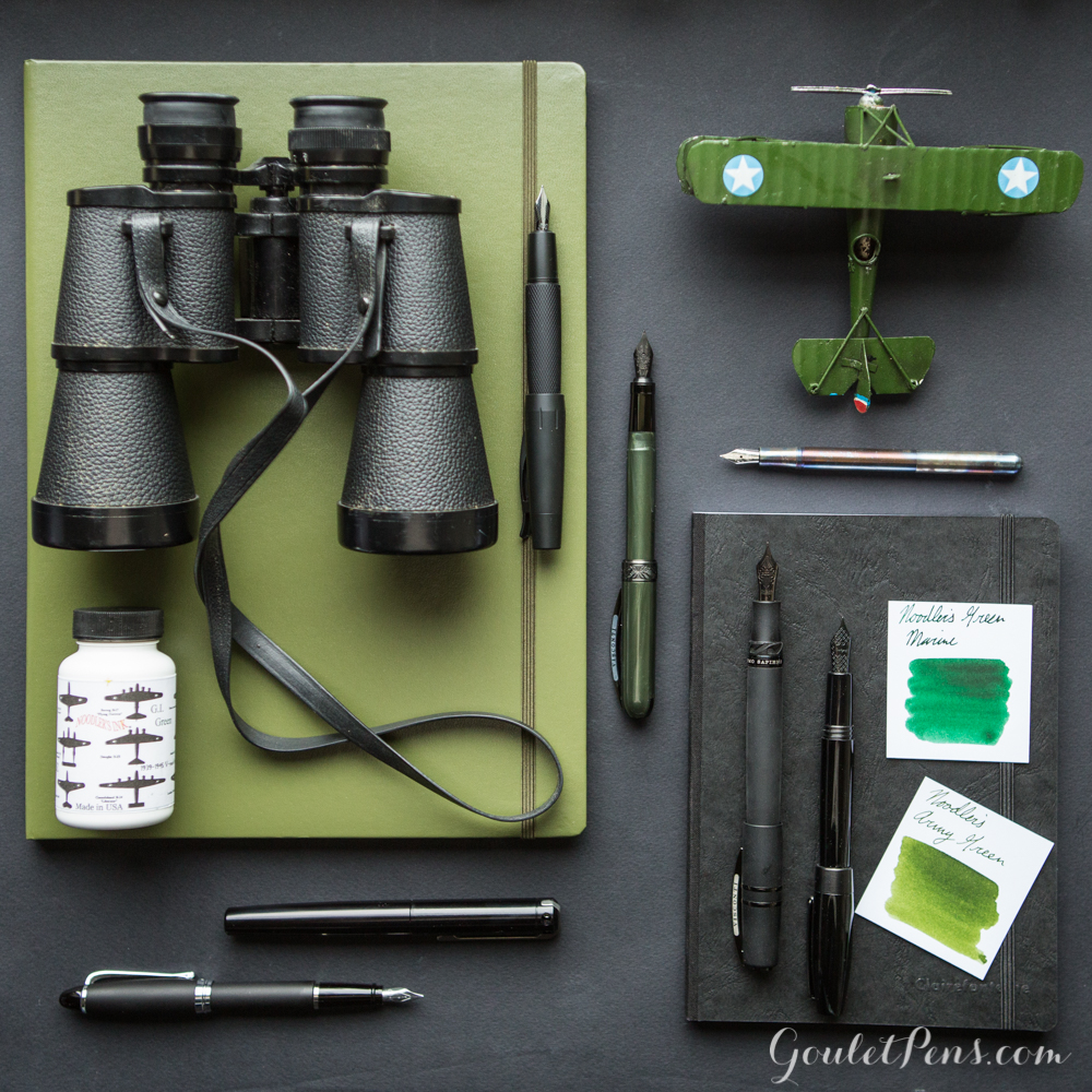 Army green and stealthy black fountain pens arranged in a flat lay display alongside ink and notebooks.