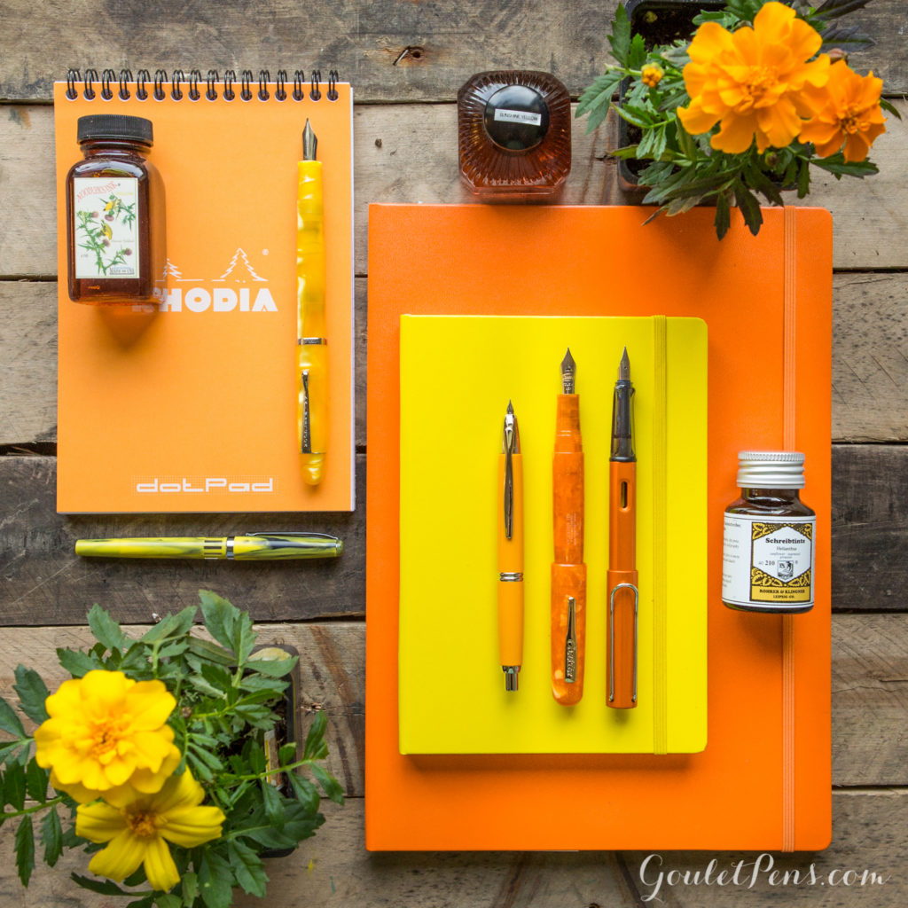 Colorful flat lay of orange and yellow fountain pens, paper, and ink with Marigold flowers.
