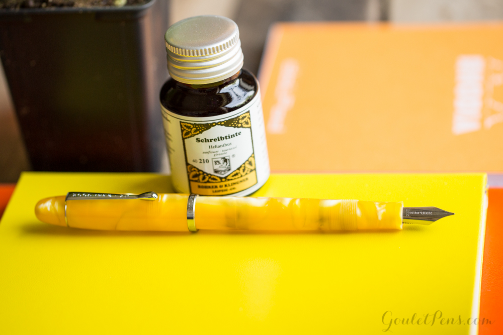 Noodler's Neponset Fer deLance Yellow in a colorful flat lay of orange and yellow fountain pens, paper, and ink with Marigold flowers.