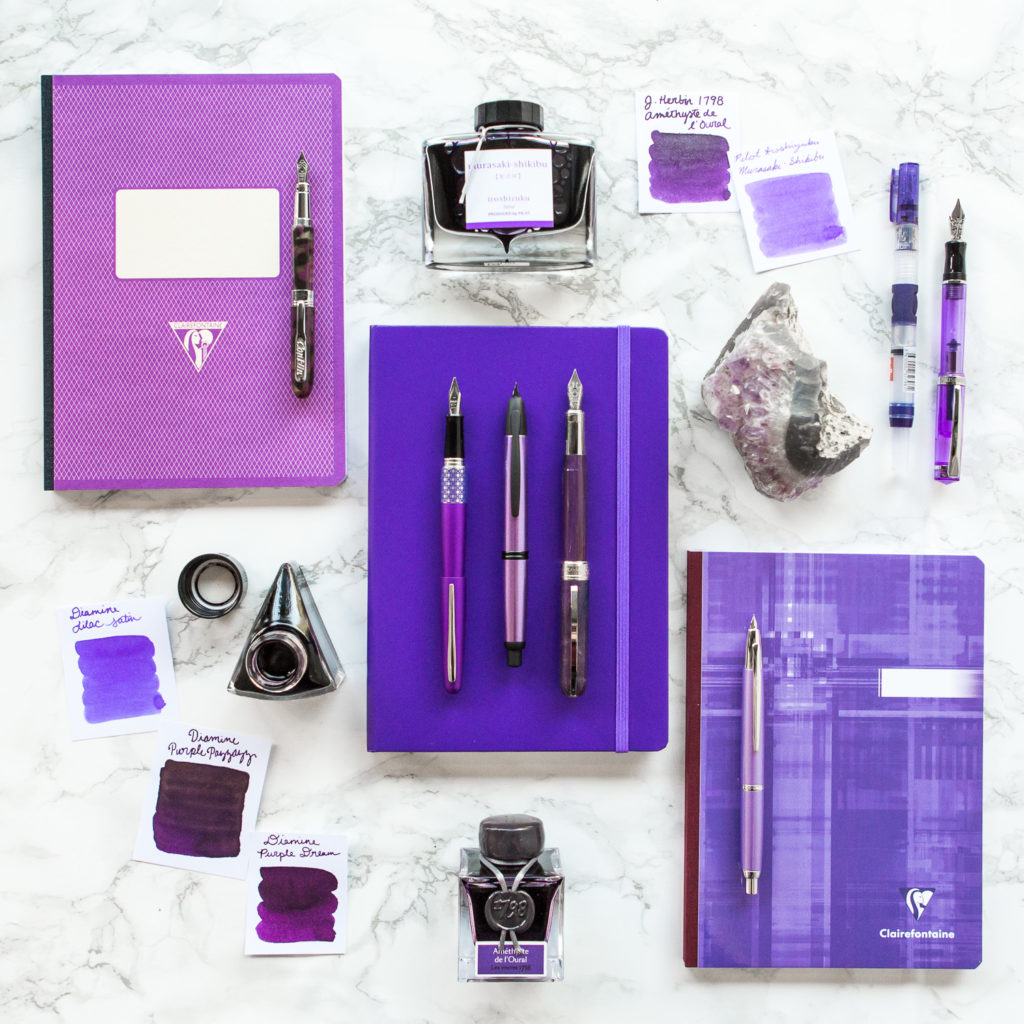 A purple sparkle inspired flat lay of fountain pens, notebooks, and ink.