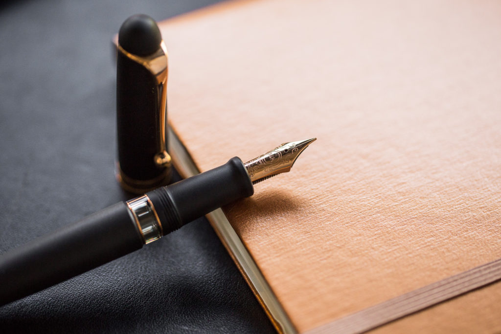 A flat lay of professional power pens, fountain pens, notebooks, and ink.