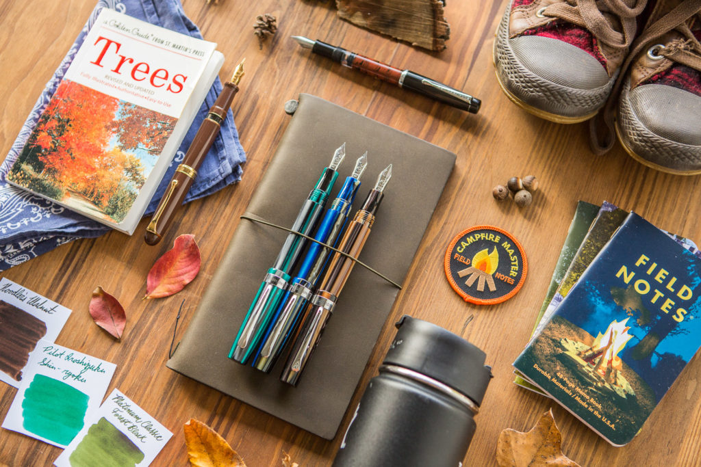 A flat lay of camping and outdoor themed pens, fountain pens, notebooks, and ink.