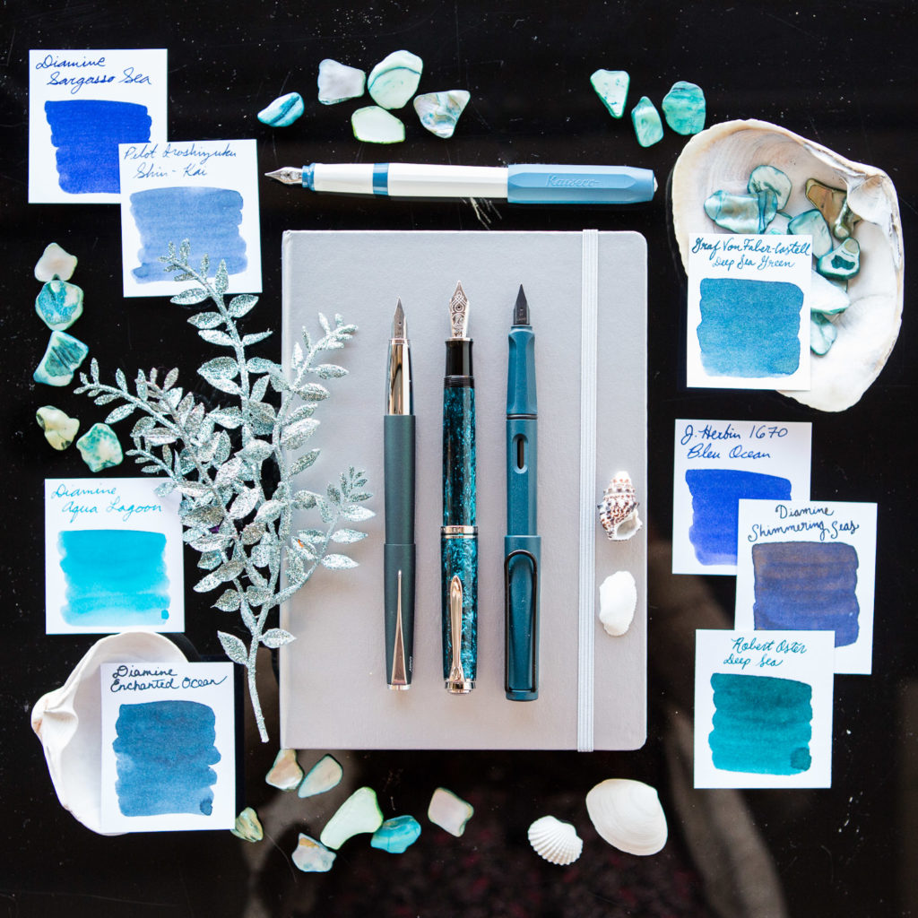 A deep sea themed flat lay of teal and blue fountain pens, notebooks, and ink.
