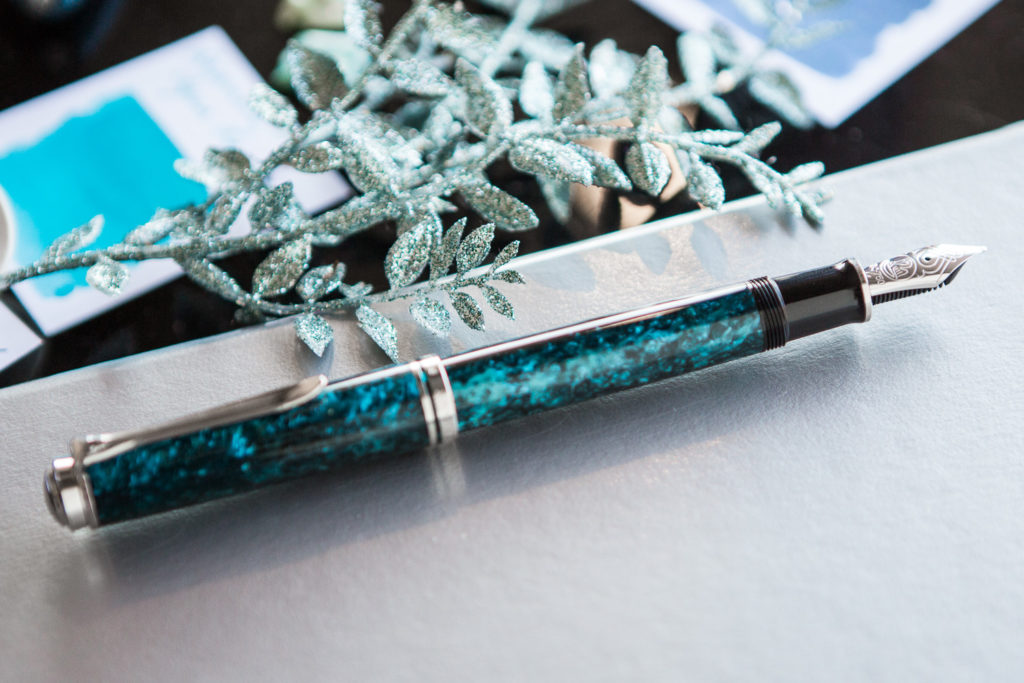 Pelikan M805 Ocean Swirl in a deep sea themed flat lay of teal and blue fountain pens, notebooks, and ink.