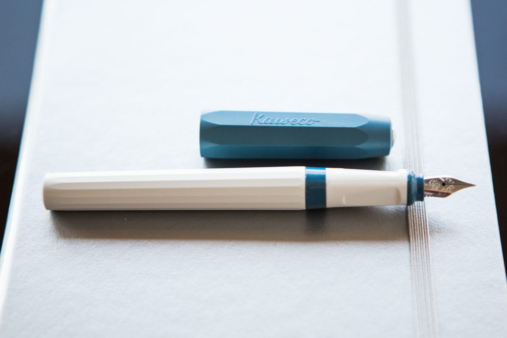 Kaweco Perkeo fountain pen in a deep sea themed flat lay of teal and blue fountain pens, notebooks, and ink.