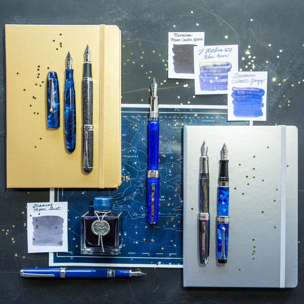 A starry flat lay of galaxy inspired fountain pens, notebooks, and ink.