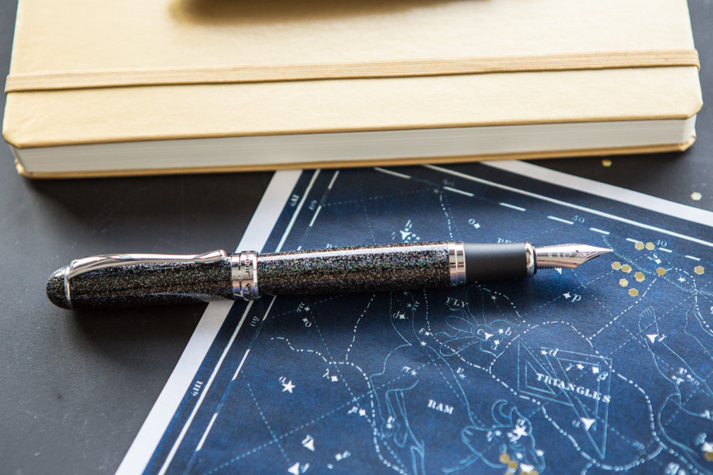 Jinhao x750 in a starry flat lay of galaxy inspired fountain pens, notebooks, and ink.