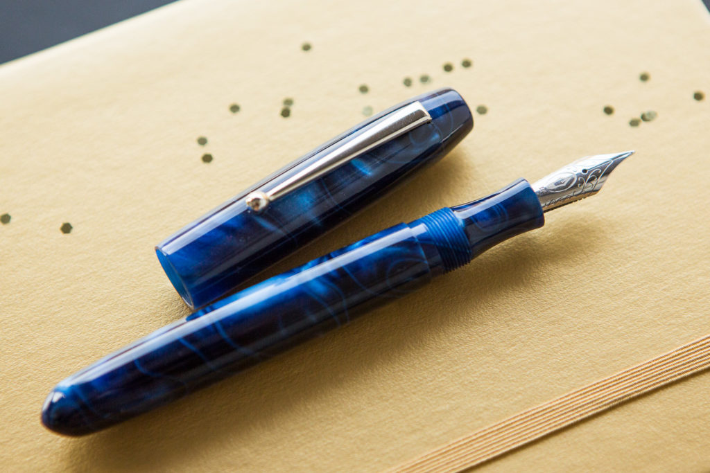 Edison Collier Fountain Pen Blue Steel in a starry flat lay of galaxy inspired fountain pens, notebooks, and ink.