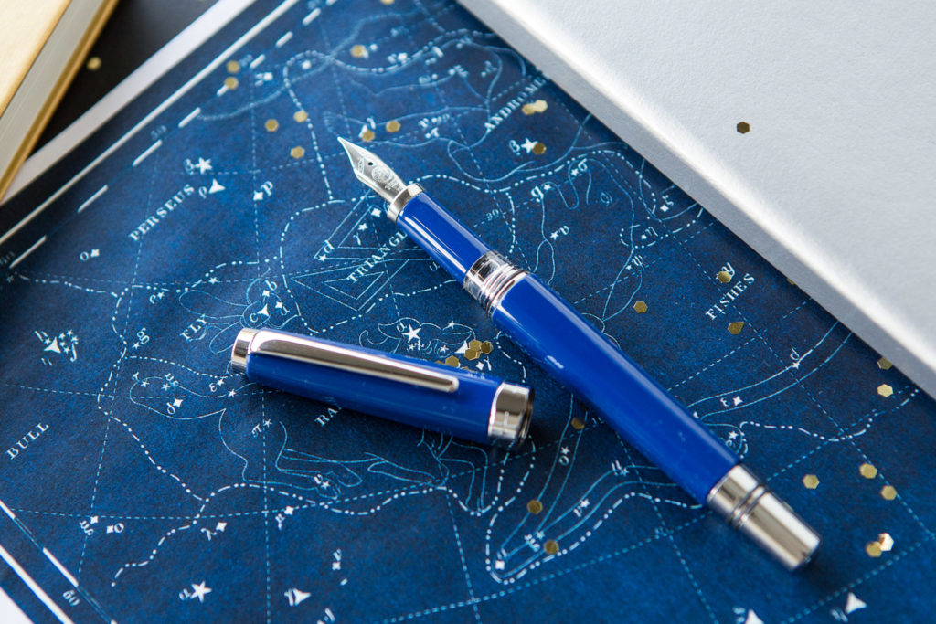 TWSBI Classic Sapphire in a starry flat lay of galaxy inspired fountain pens, notebooks, and ink.