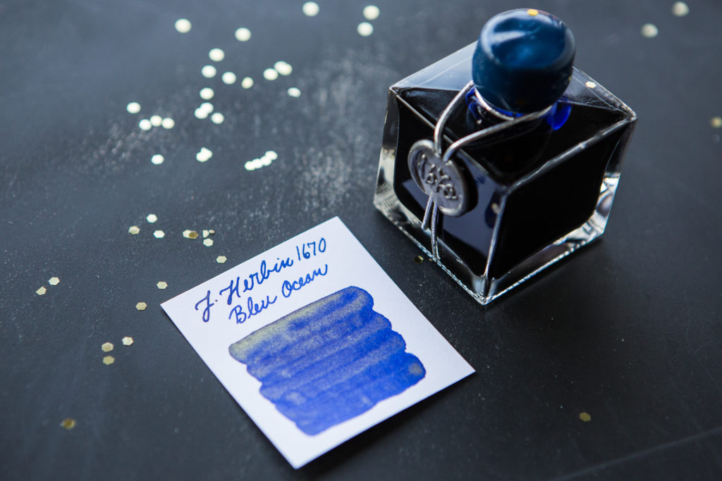 J. Herbin 1670 Blue Ocean in a starry flat lay of galaxy inspired fountain pens, notebooks, and ink.