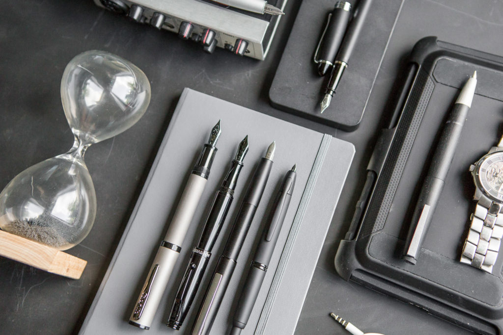 A flat lay of black and stealthy fountain pens, notebooks, and ink for the techie.