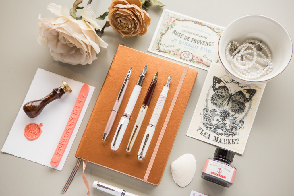 A flat lay of vintage ivory colored pens, fountain pens, notebooks, and ink.