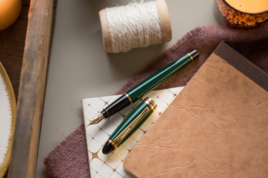 A cozy, winter themed flat lay of warm toned fountain pens, notebooks, and ink.