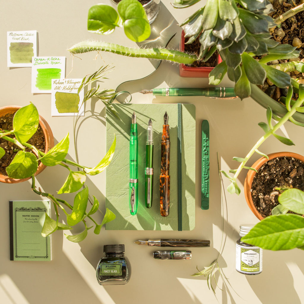 A plant themed flat lay of green fountain pens, notebooks, and ink.