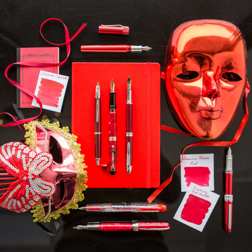 A red masquerade themed flat lay of fountain pens, notebooks, and ink.