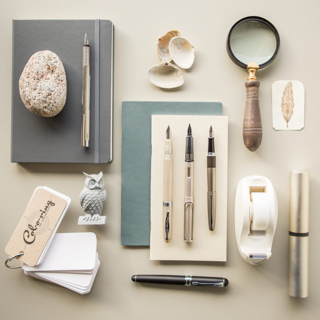 A neutral colored, minimal flat lay of fountain pens, notebooks, and ink.