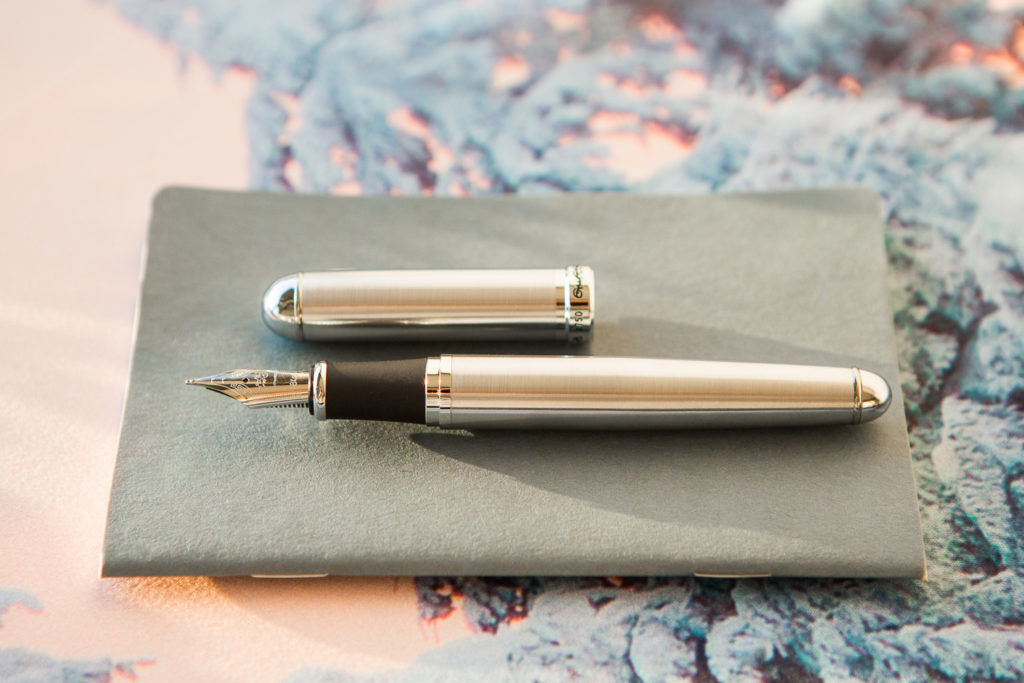 Nordic blue and rose gold fountain pens, notebooks, and ink in a winter flat lay.