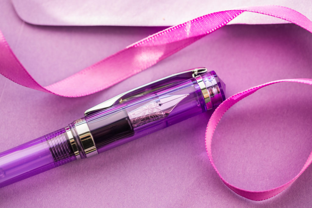An Ultra Violet Pantone Color of the Year product themed flat lay of fountain pens, notebooks, and ink.
