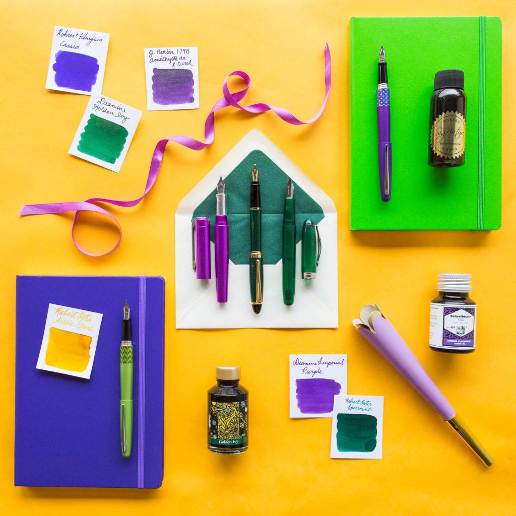 A Mardi Gras themed flat lay of green, purple, and gold fountain pens, notebooks, and ink.