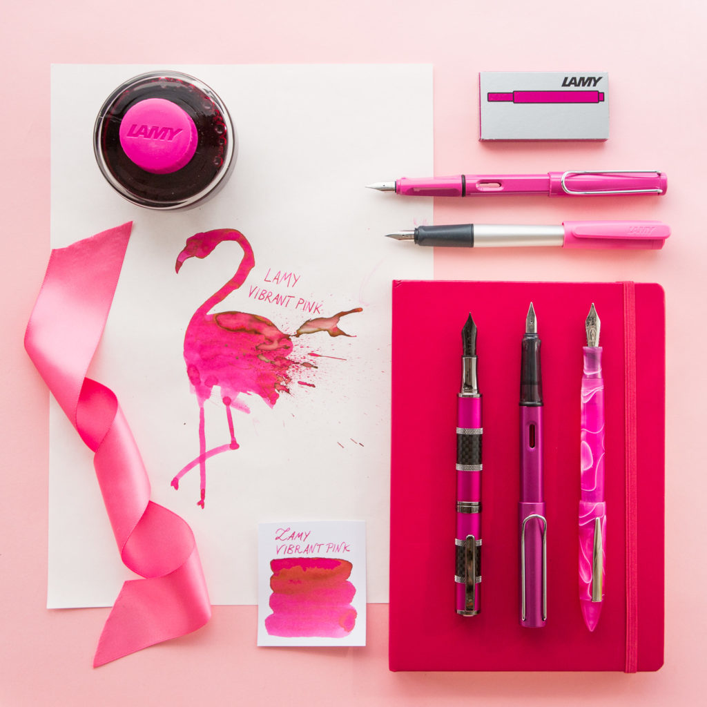 Flamingo pink flat lay of fountain pens, notebooks, and ink.