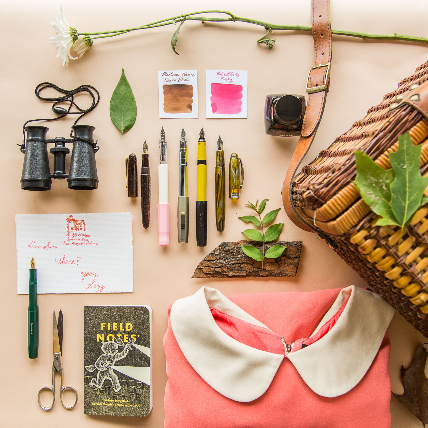 Flat lay arrangement of Wes Anderson inspired fountain pens, notebooks, and paper.