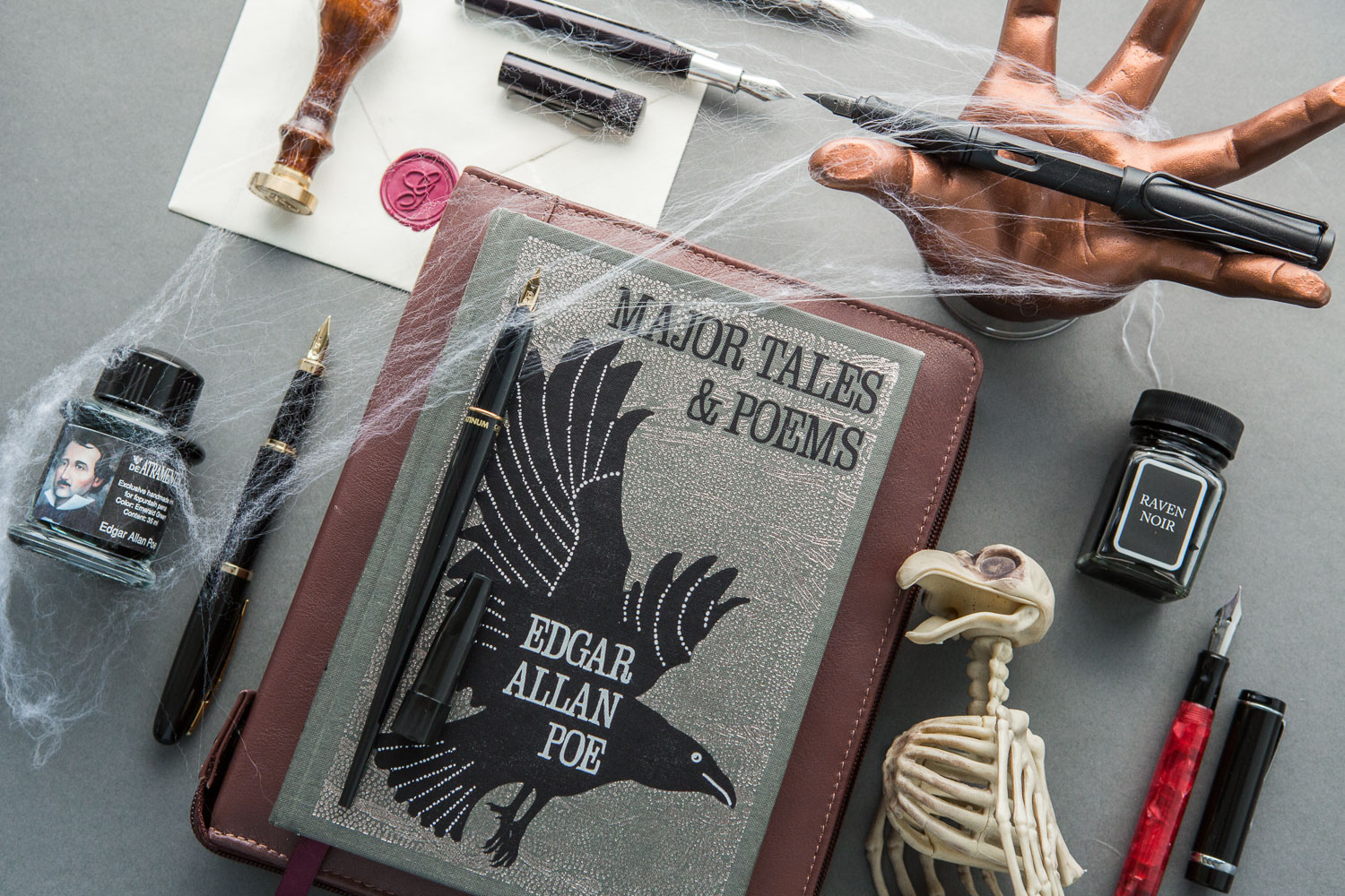 Flat lay of Edgar Allan Poe themed writing accessories with fountain pens and fountain pen ink.