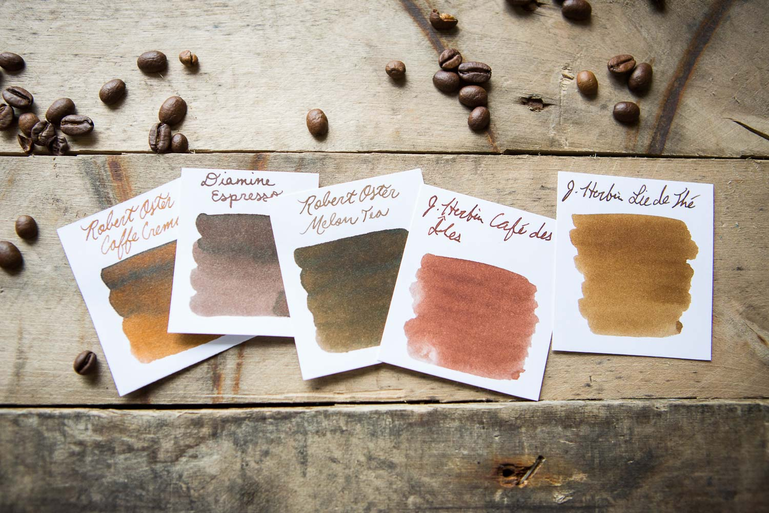 Rich brown fountain pen ink swabs in a coffee and tea inspired flat lay of fountain pens, notebooks, and ink.