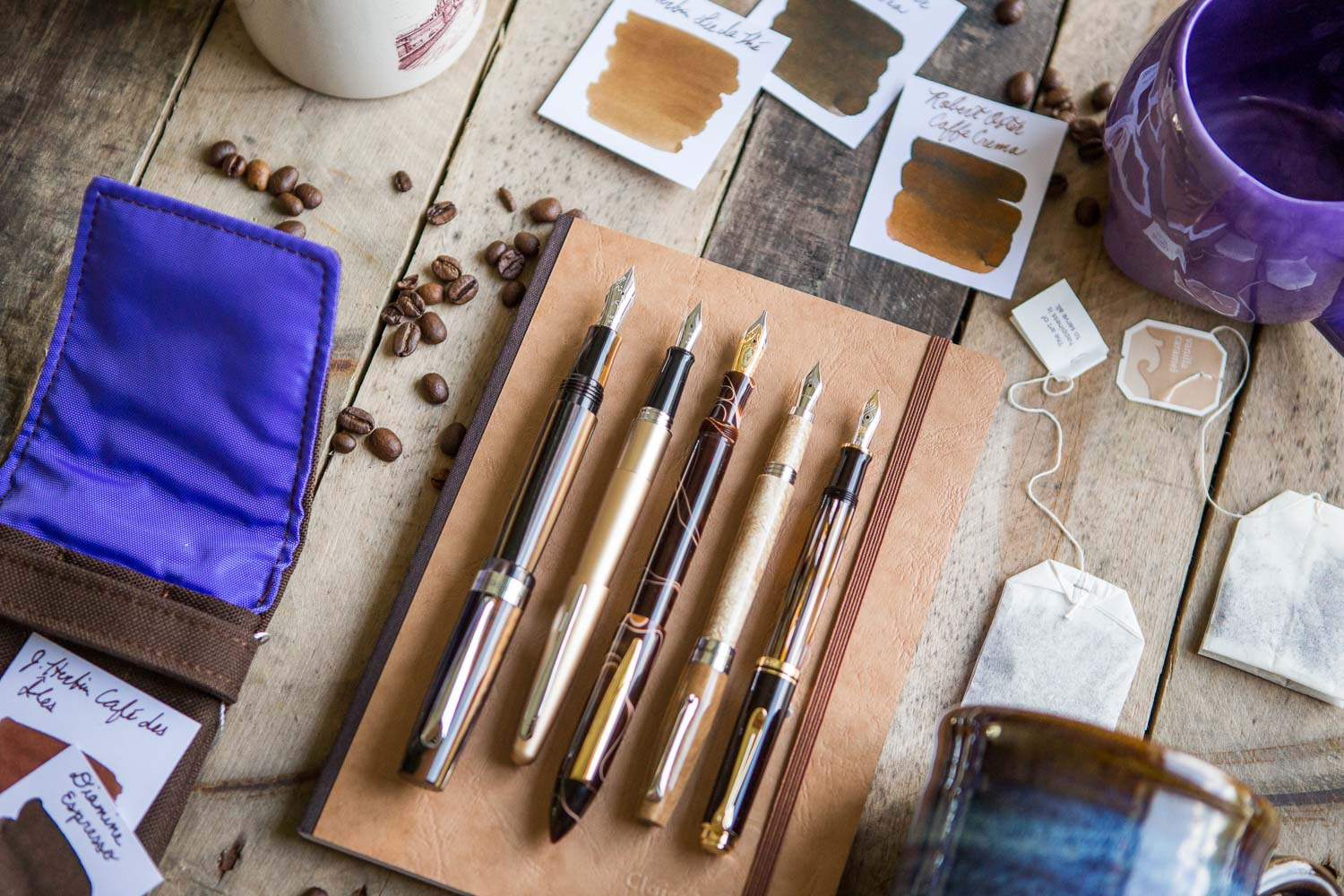 A coffee and tea inspired flat lay of fountain pens, notebooks, and ink.