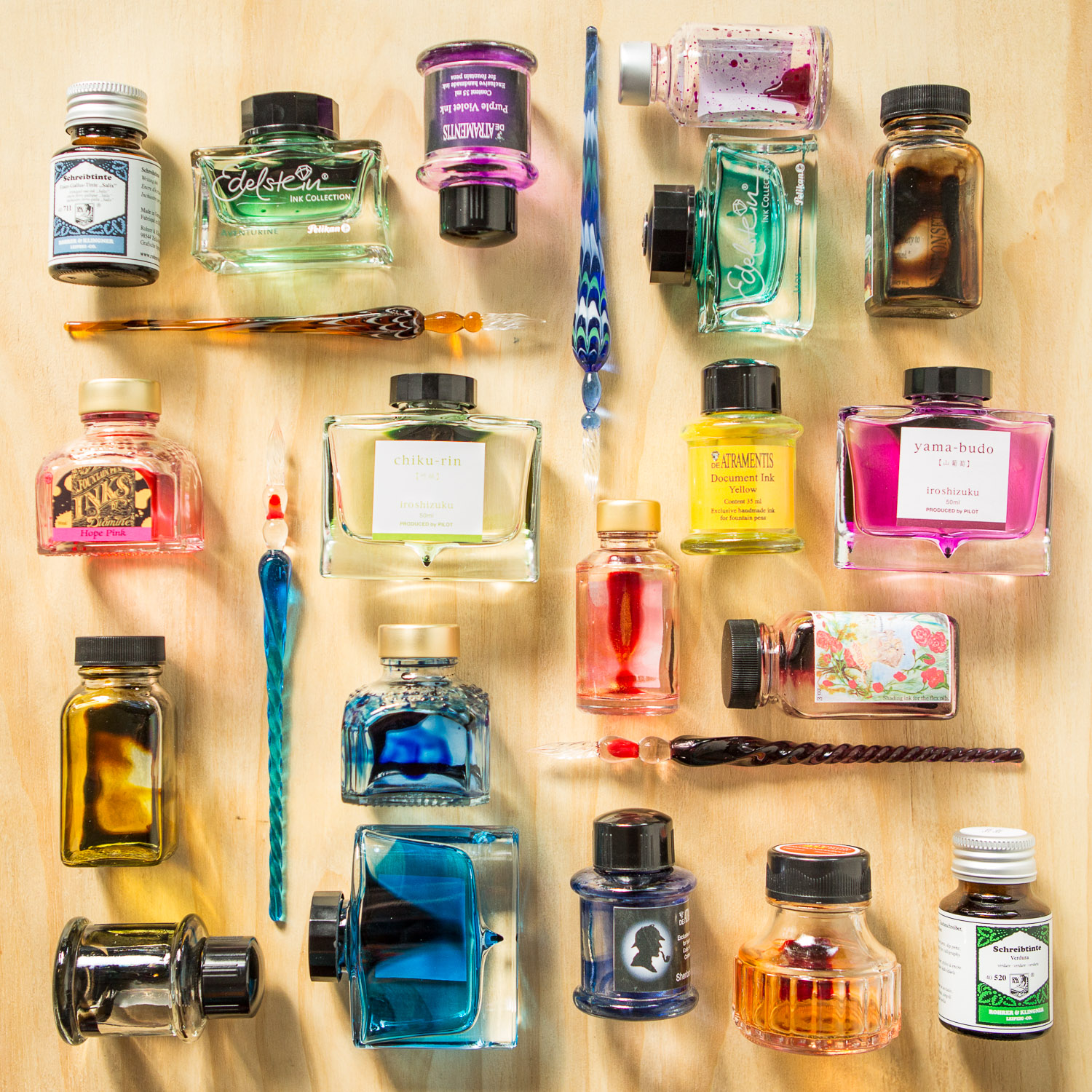 Colorful flat lay of empty fountain pen ink bottles and glass dip pens.
