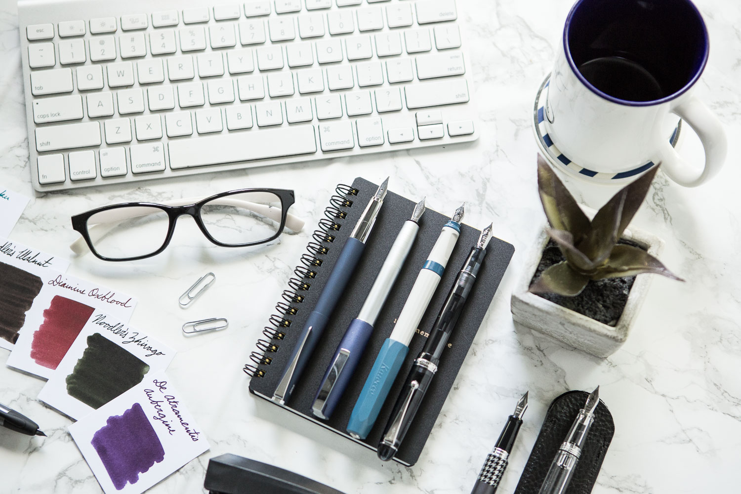 An office inspired flat lay of fountain pens, notebooks, and ink.