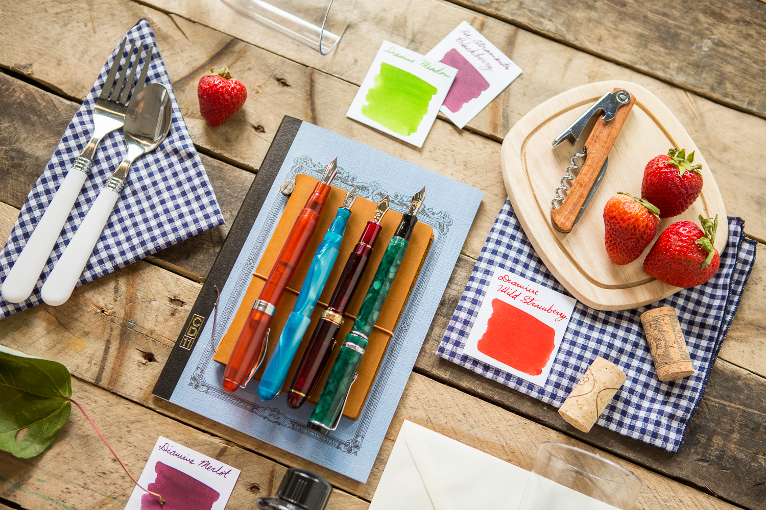 A colorful picnic inspired flat lay of fountain pens, notebooks, and ink.