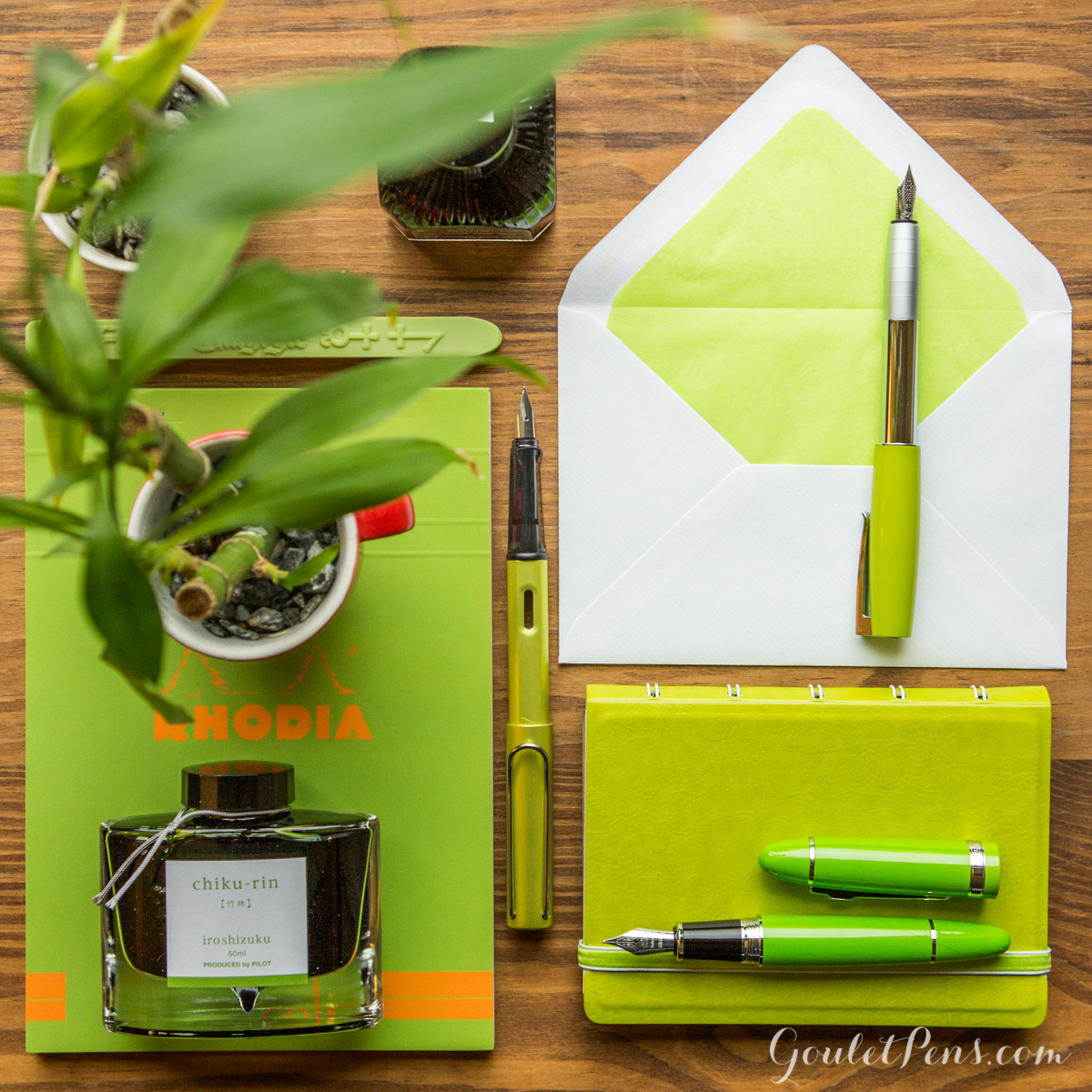 A flat lay arrangement of fountain pens, notebooks, and ink in an array of light bamboo greens and lime hues.