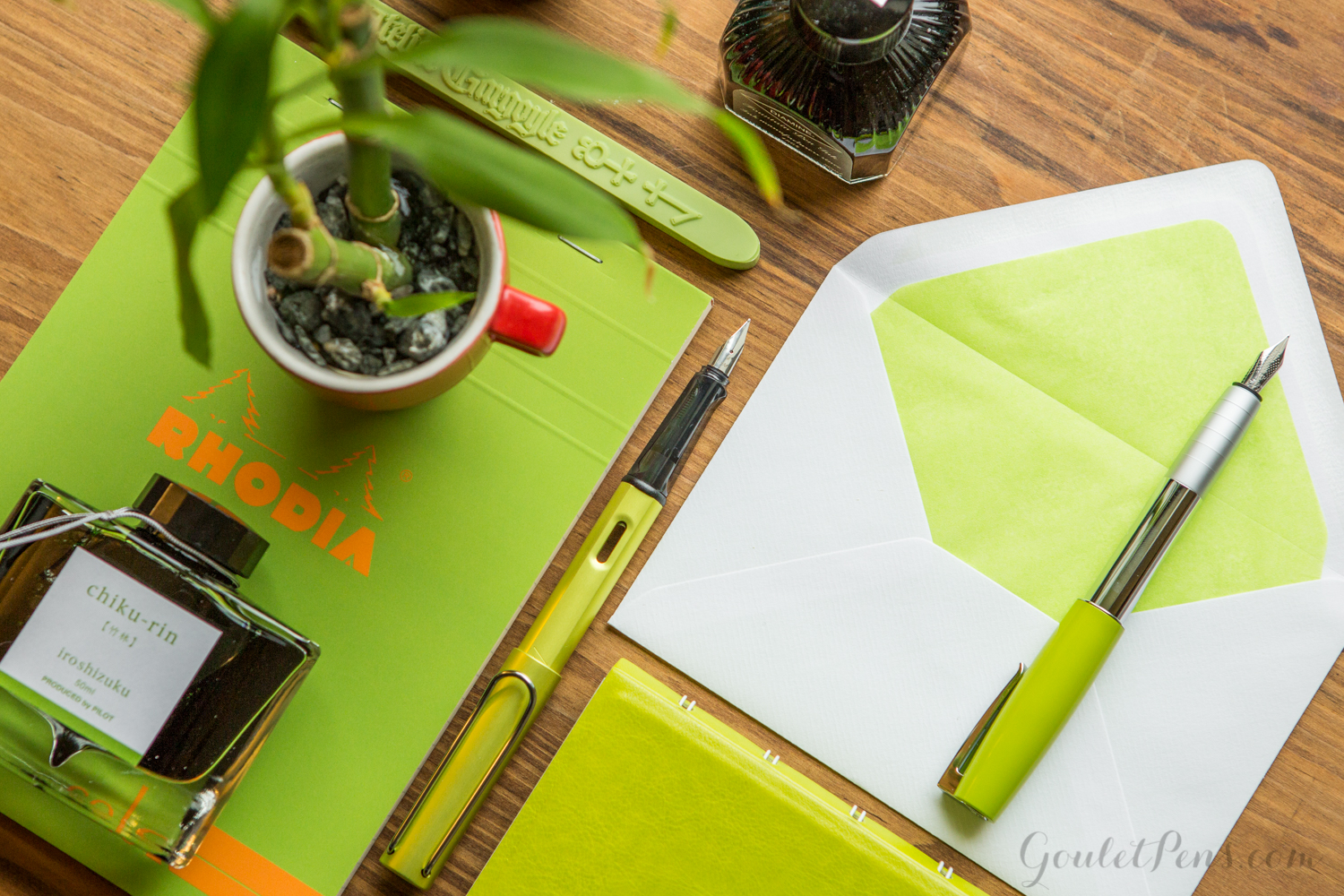 Faber-Castell Loom Piano Lime in a flat lay arrangement of fountain pens, notebooks, and ink in an array of light bamboo greens and lime hues.
