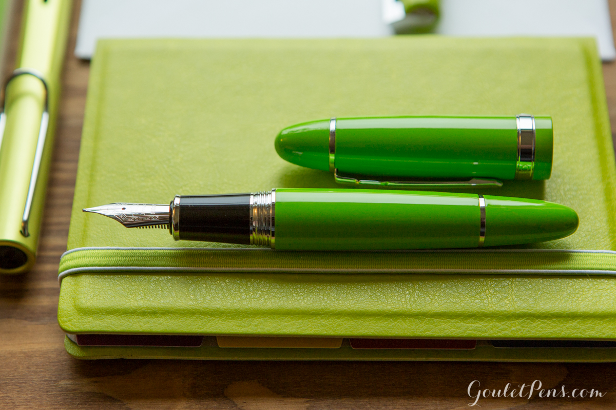 Lamy Al-Star Charged Green in a flat lay arrangement of fountain pens, notebooks, and ink in an array of light bamboo greens and lime hues.