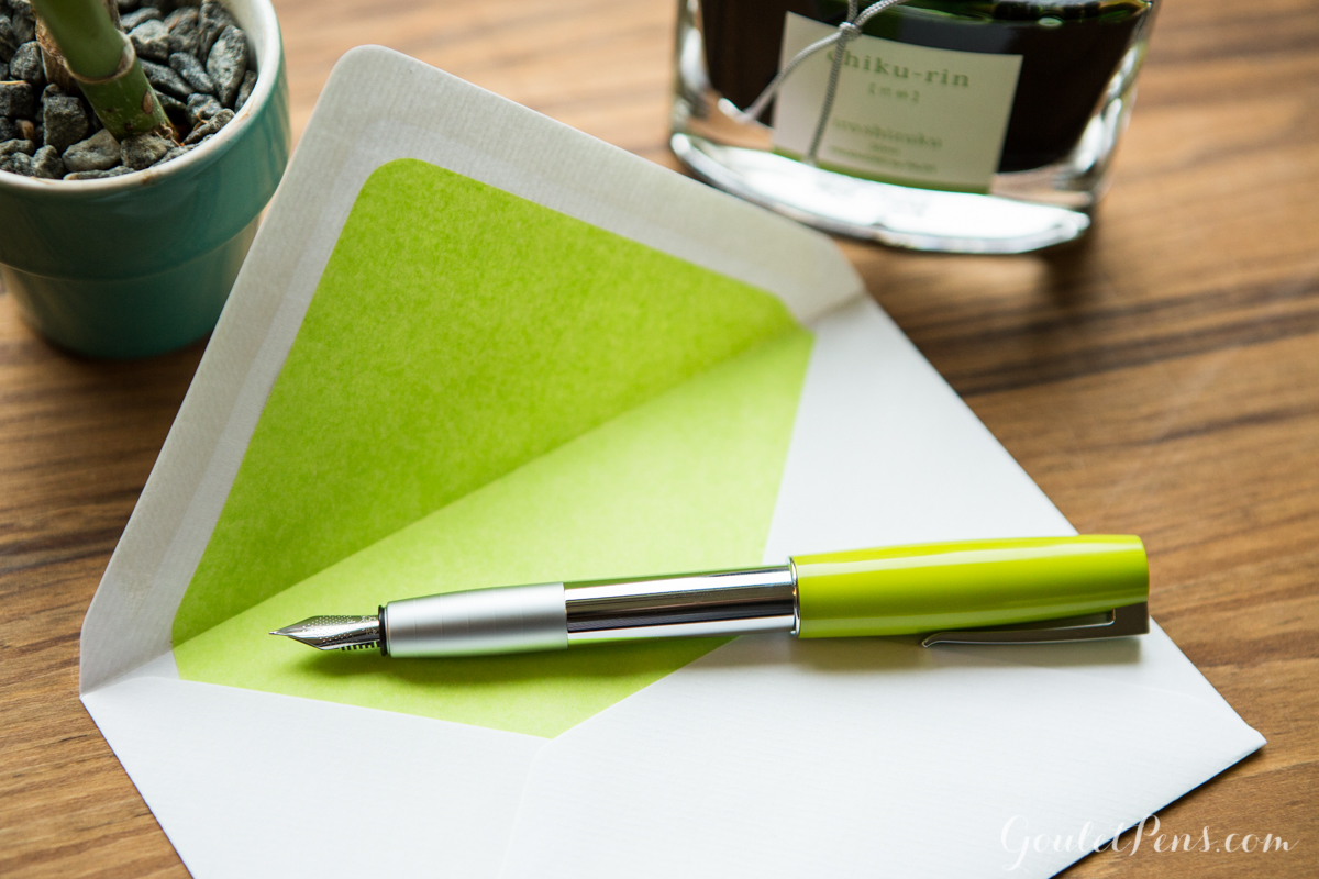 Jinhao 159 Green in a flat lay arrangement of fountain pens, notebooks, and ink in an array of light bamboo greens and lime hues.