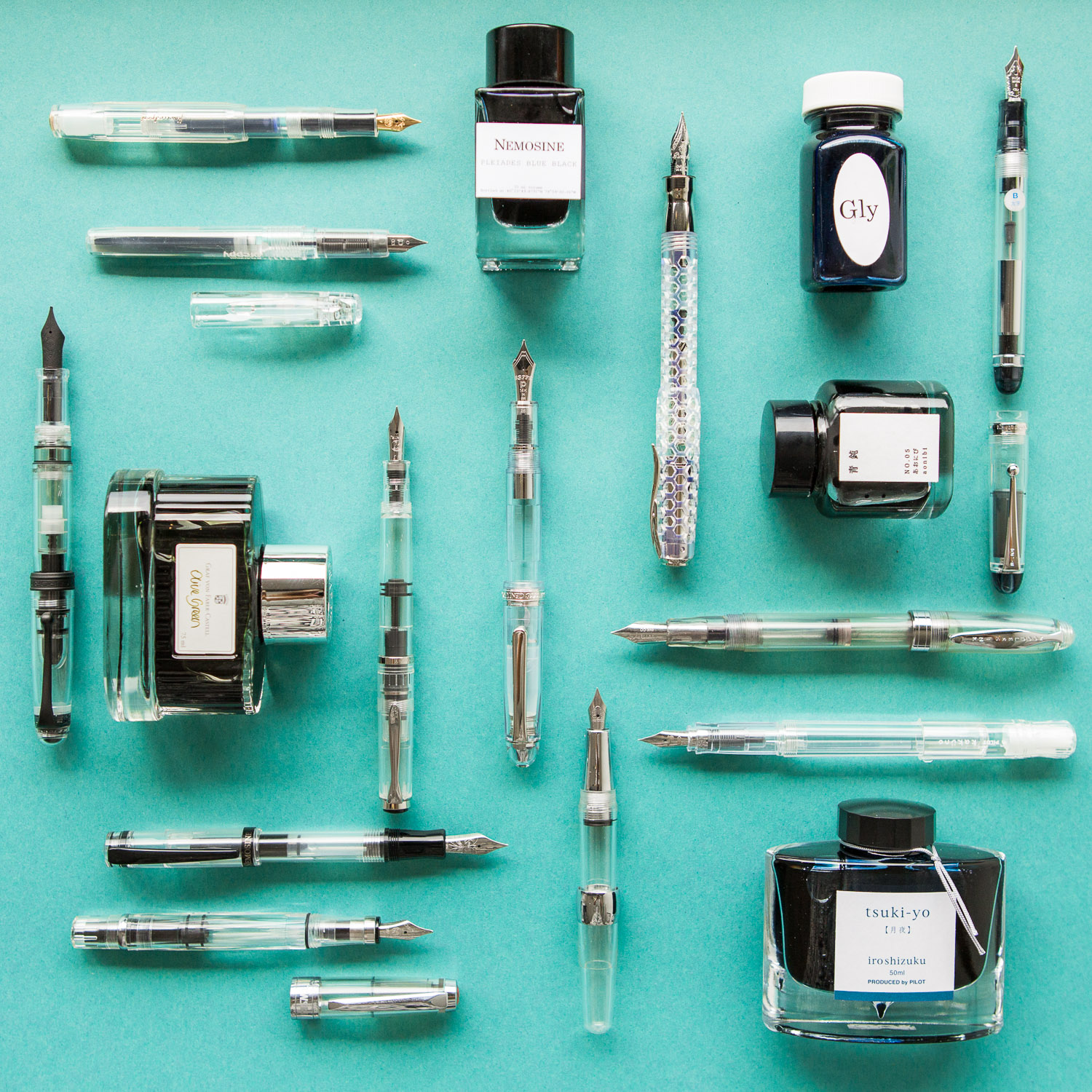Arrangement of clear demonstrator fountain pens and ink.