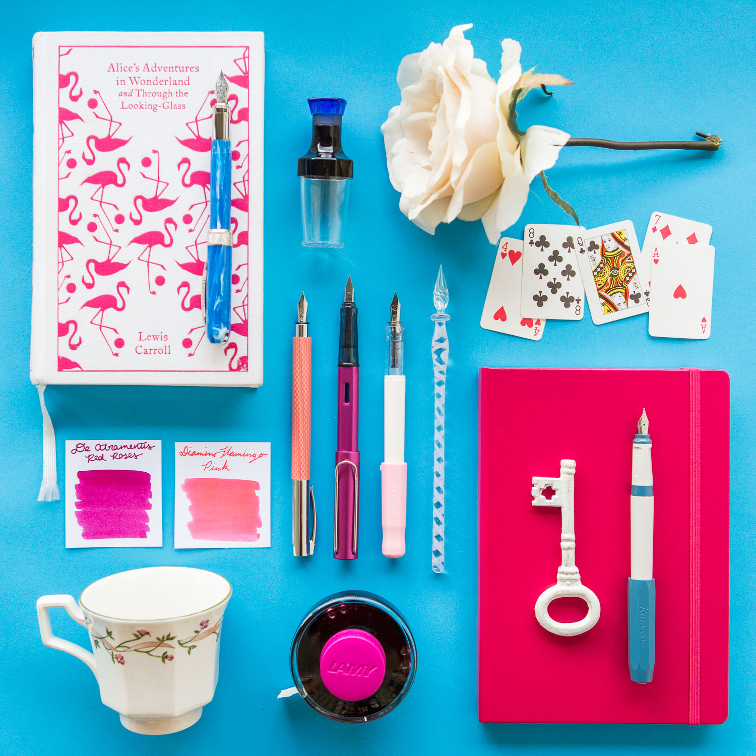 Alice in Wonderland themed flat lay of fountain pens, notebooks, and writing products.
