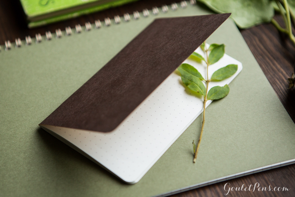 Goulet Notebook in a flat lay arrangement of green and brown rustic fountain pens, notebooks, and ink in a woodsy theme.