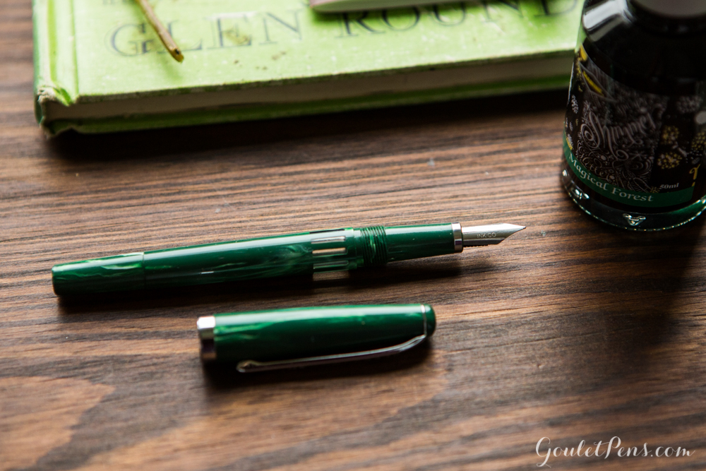Noodler's Jade Nib Creaper in a flat lay arrangement of green and brown rustic fountain pens, notebooks, and ink in a woodsy theme.