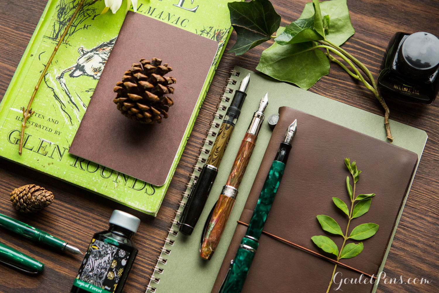 Flat lay arrangement of green and brown rustic fountain pens, notebooks, and ink in a woodsy theme.