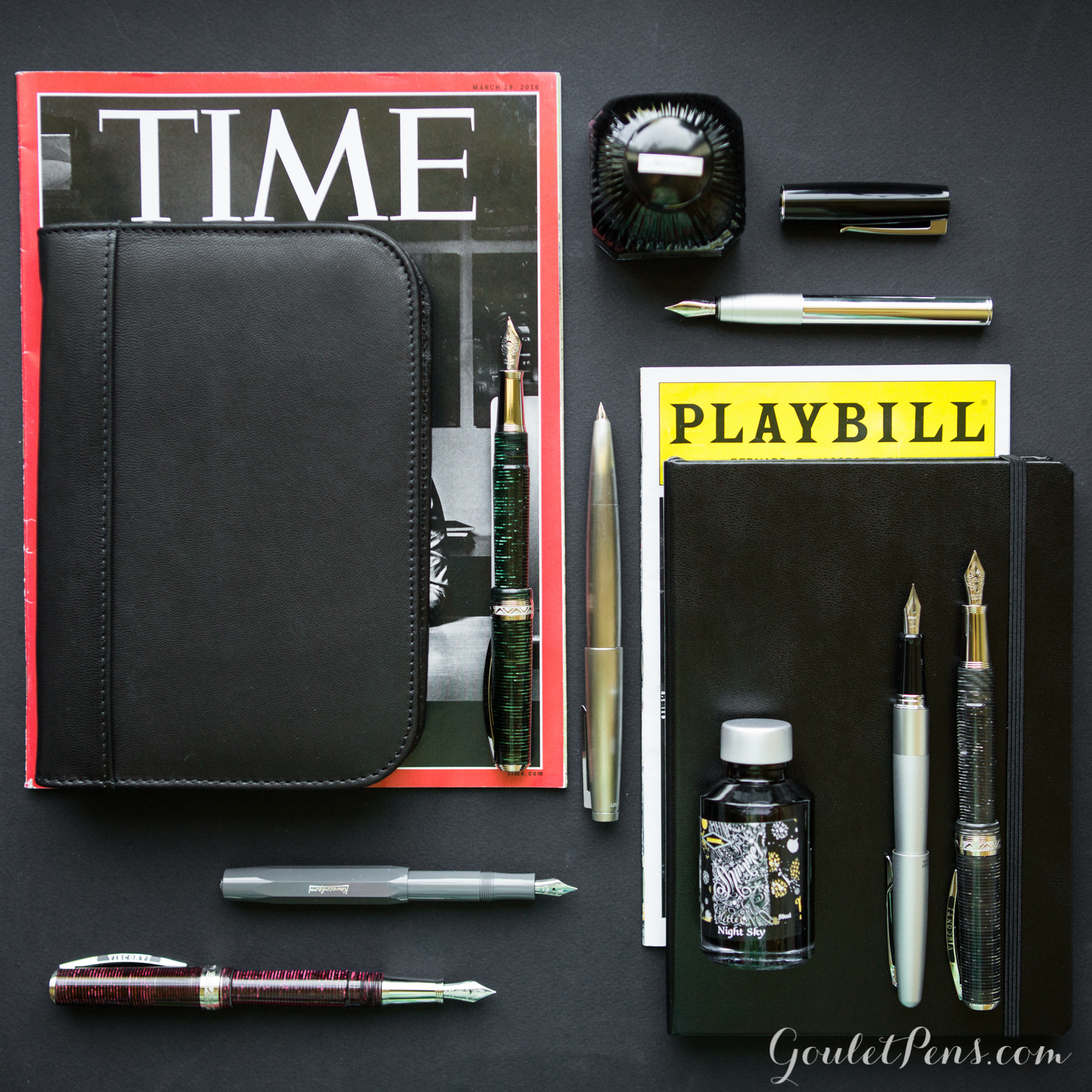 NYC themed flat lay arrangement of fountain pens, notebooks, and ink in an array of professional grey and black colors.