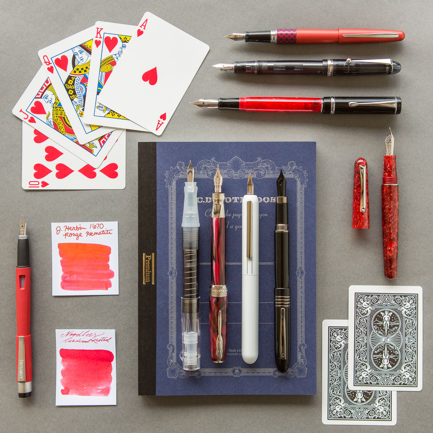 Playing card themed spread of fountain pens, notebooks, and ink.
