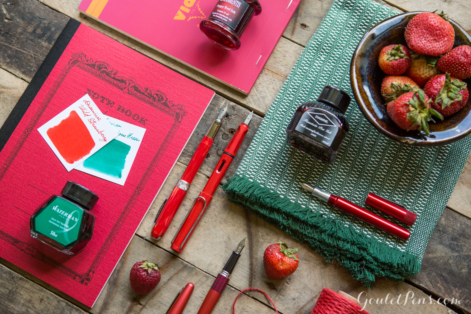 Pilot Metropolitan in a strawberry themed flat lay arrangement of fountain pens, notebooks, and ink in an array of reds and green colors.