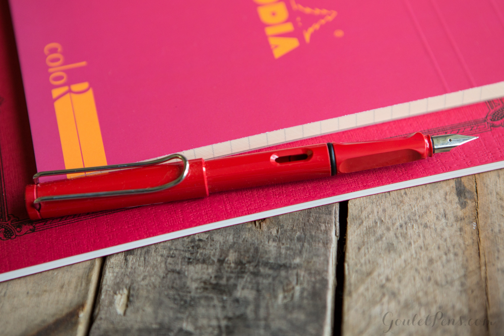 A strawberry themed flat lay arrangement of fountain pens, notebooks, and ink in an array of reds and green colors.