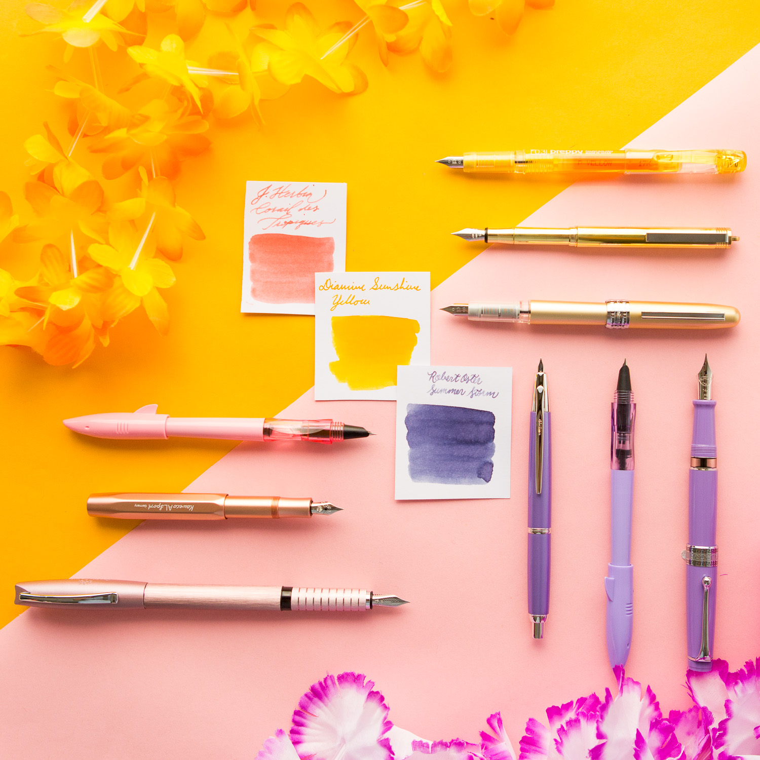 A summery spread of pink, purple, and orange fountain pens and accessories.